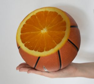 un ballon de basket, coupé, avec un orange à l'intérieur